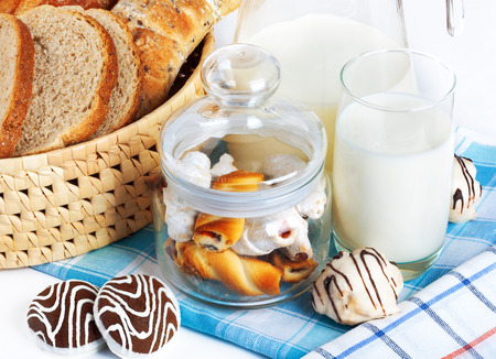 Sliced bread and chocolate chip cookies with milk on checkered tablecloth photo