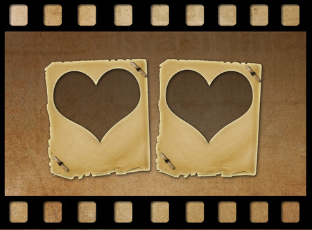 alienated: Old paper slides in the form of hearts on abstract grunge background
