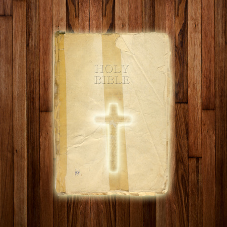 Glowing holy cross on abstract wooden background photo