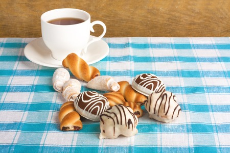 afternoon fancy cake: Cup of tea and delicious cookies on blue checkered tablecloth Stock Photo