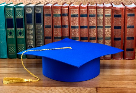 mortar cap: Graduation mortarboard on top of stack of books on abstract background of wall