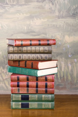 volumes: Richly decorated volumes of books with a gold lettering on the beautiful wooden shelf