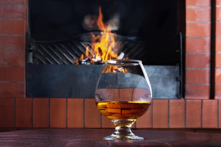 fire brick: Two glasses of cognac on the old brick fireplace with a bright fire Stock Photo