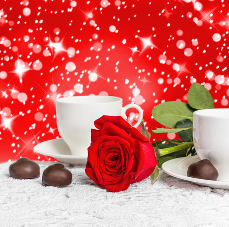Beautiful red rose and cup of hot tea with chocolate on abstract background