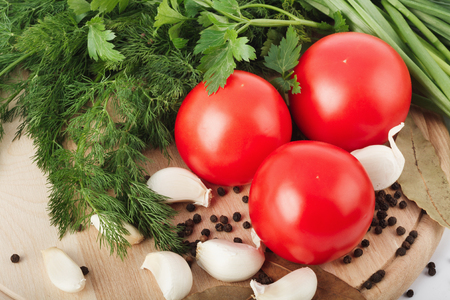 Fresh raw tomatoes, green onions, parsley and dill on a cutting board