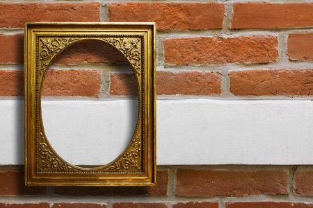Gilded wooden frame for pictures on old brick stone wall Stock Photo