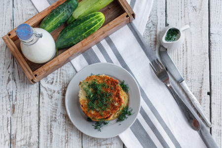 Delicious pancakes from courgettes and fresh vegetables with sour cream and dill on the table top view