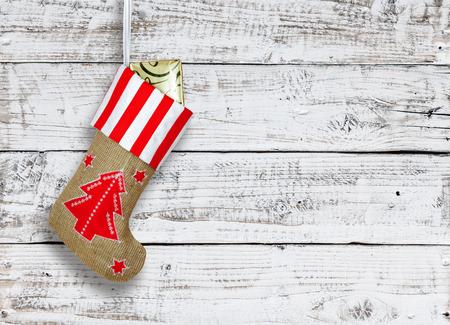 Bota de Navidad roja con regalos en la pared de madera de fondo