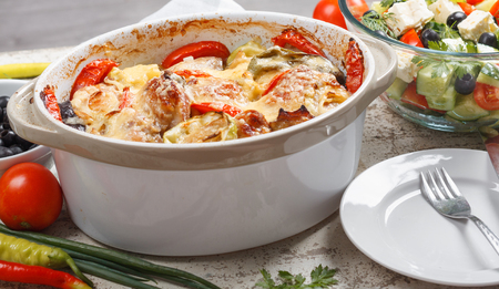 Traditional tasty rustic stew of chicken and vegetables, decorated with tomatoes, peppers and cheese.  With Greek salad and black olives Stock Photo