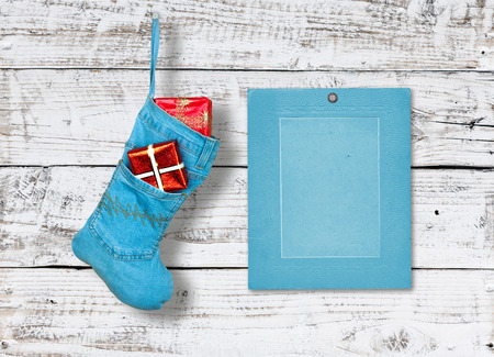 Blue denim christmas boot with gifts on background wooden wall