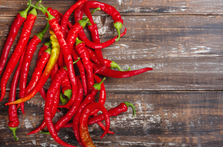 Chili red spicy hot pepper on wooden background.  Top view flat lay group objects