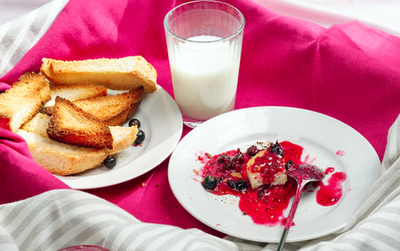 Delicious toasts bread with homemade currant jam on bright crimson tablecloth. Remains of breakfast Stock Photo