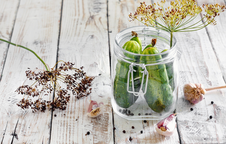 Preserved cucumbers in glass jar with dill and garlic on wooden table