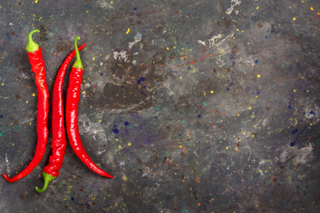 The composition of chili red hot peppers on the stone table top. Top view flat lay group objects