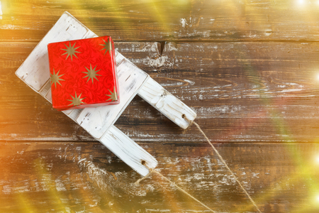 Old wooden toy sled with gift boxes on  wooden background. Top View Flat Lay Group Objects