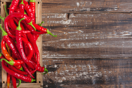 The composition of chili red hot peppers on wooden table. Top view flat lay group objects Stock Photo
