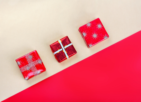 Golden gift box on  bright red background.Top view flat lay group objects