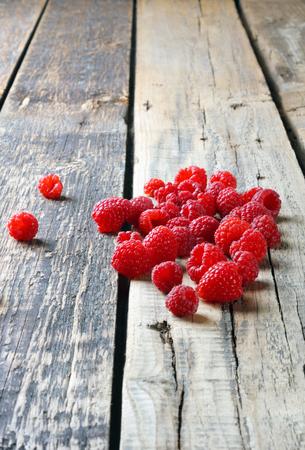 Fresh juicy tasty raspberries scattered on  wooden table