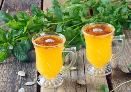 Healthy pumpkin fruit smoothie with seeds and mint leaves on old wooden table Stock Photo