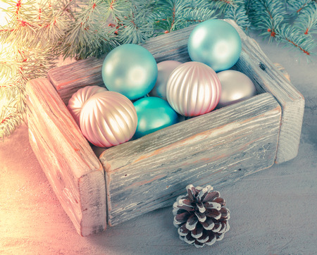 Old wooden vintage box with beautiful pink and blue Christmas balls on a background with green fir branches