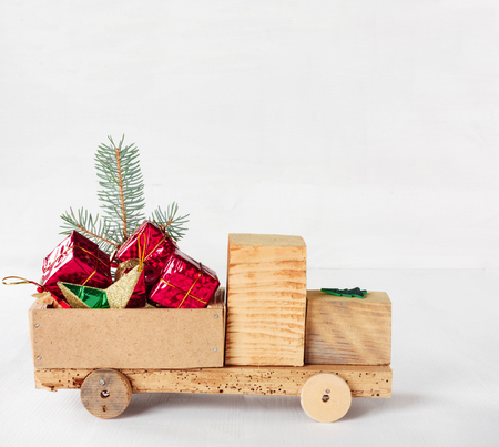 Old vintage toy wooden car with gifts and Christmas balls on  white background