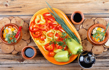 Traditional rustic home vegetable stew with raw vegetables, spices in clay pots with red  wine on old vintage wooden table.Top view flat lay group objects
