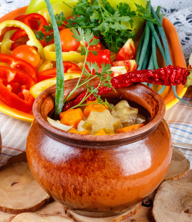 Traditional rustic home  gulyas, with raw vegetables and spices in clay pots on  old vintage wooden table.