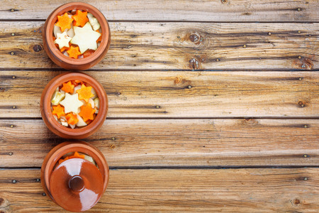 Traditional rustic home vegetable  ragout in three clay pots on old vintage wooden table. Top view flat lay group objects Stock Photo