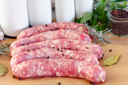 Delicious rustic raw  meat sausages in on parchment paper, with bay leaves and fresh herbs in the kitchen.