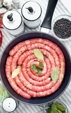 Delicious rustic raw  meat sausages in frying pan, with bay leaves and fresh herbs in the kitchen. Top view flat lay group objects