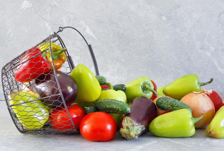 Harvest of ripe pepper, tomato, eggplant and onion in  metal basket on stone table