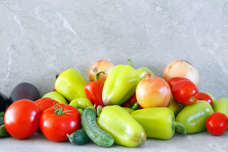 Harvest of ripe pepper, tomato, eggplant and onion  on stone table Stock Photo