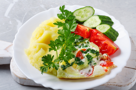 Hot tasty mashed potatoes with scrambled eggs, tomatoes, cucumbers and fresh parsley in  plate on stone countertop