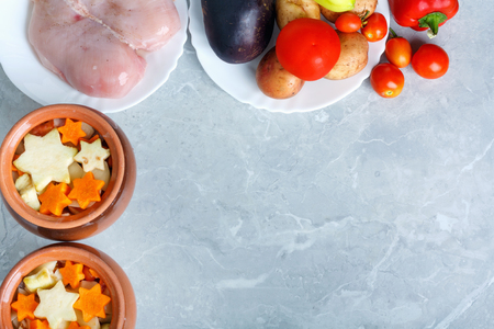 Traditional rustic home vegetable  ragout in three clay pots on beautiful stone table top. Top view flat lay group objects Stock Photo