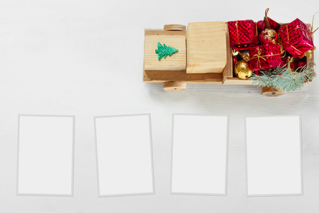 Old vintage toy wooden car with gifts and Christmas balls, paper frame on white background, Top View Flat Lay Group Objects
