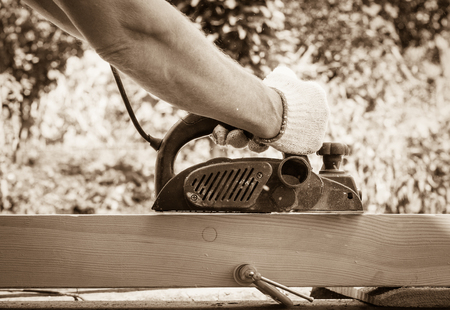 Carpenter working with electric planer on wooden plank in outdoor.