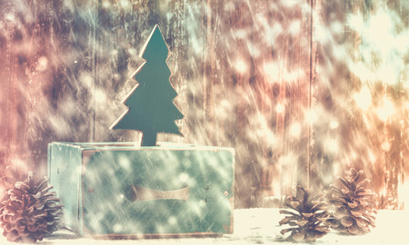 Old box with vintage Christmas handmade toys on a withered wooden background with snow and lights Stock Photo