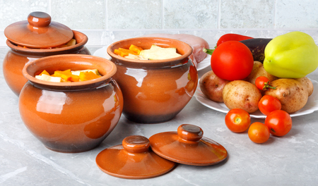 Traditional rustic home vegetable  ragout in three clay pots on beautiful stone table top.