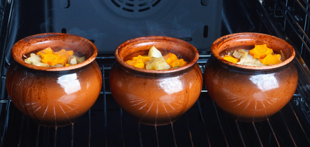 Traditional rustic home vegetable  ragout in three clay pots in hot modern oven