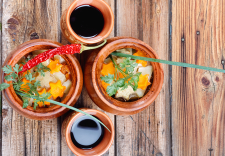 Traditional rustic home  gulyas, with raw vegetables and spices in clay pots on  old vintage wooden table. Top view flat lay group objects