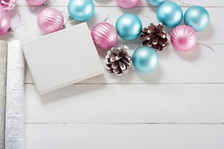Pink and blue Christmas balls with gift box and wrapping paper on old wooden table