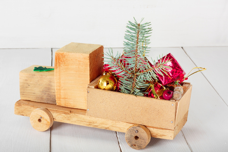Old vintage toy wooden car with gifts and Christmas balls on white background Stock Photo