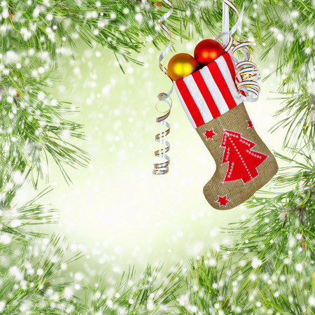 Santa Claus's New Year sock with gifts, toys and serpentine on  green background with pine