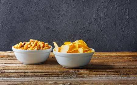 Salty snacks. Chips, crackers in bowls on wooden table on brick wall