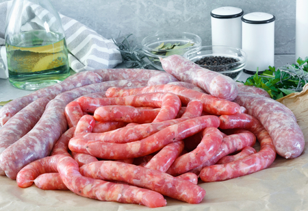 Delicious rustic raw  meat sausages in on parchment paper, with bay leaves and fresh herbs in the kitchen. Standard-Bild - 114769713