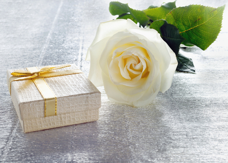 Beautiful white rose with a golden gift box for Valentine's Day or wedding