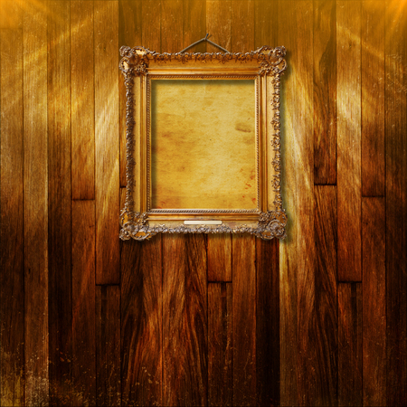 Old vintage gold ornate frame for picture on grunge wooden wall Stock Photo