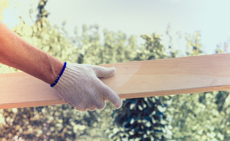 Caucasian man holding planks in the hands of bright sky  on sunny day
