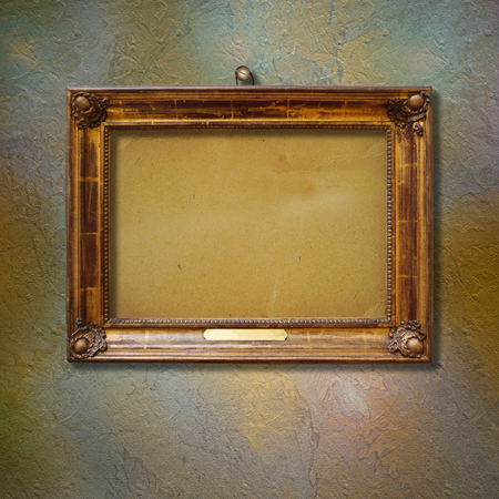 Old vintage gold ornate frame for picture on grunge stone wall Stock Photo
