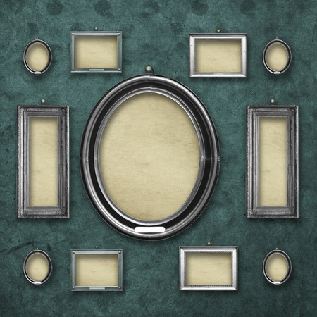 Set of wooden vintage silver baroque frames for museum exhibition on old, worn turquoise wall